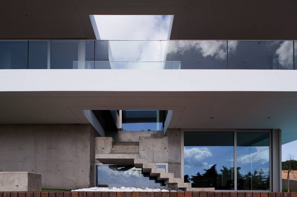 Concrete stairs provide access to the balcony, House In Lagos