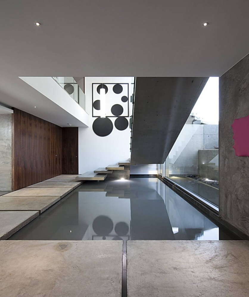 Concrete stairs over a water feature, House In Lagos