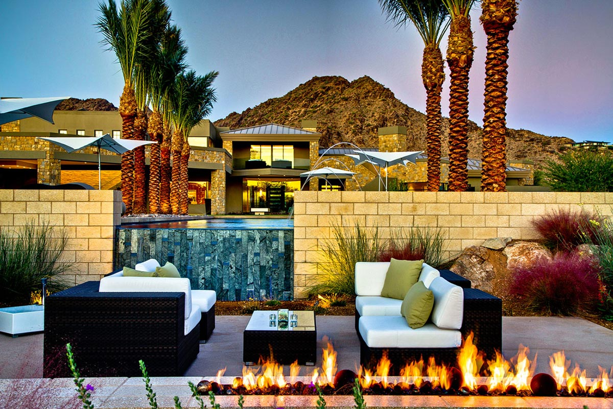 Outdoor fireplace waterfall pool seating ironwood Luxury fireplaces luxury homes