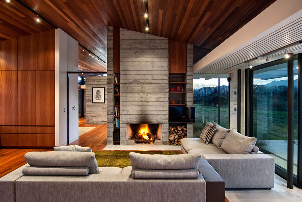 Concrete Fireplace, Sofas, Wairau Valley House in Rapaura, New Zealand by Parsonson Architects