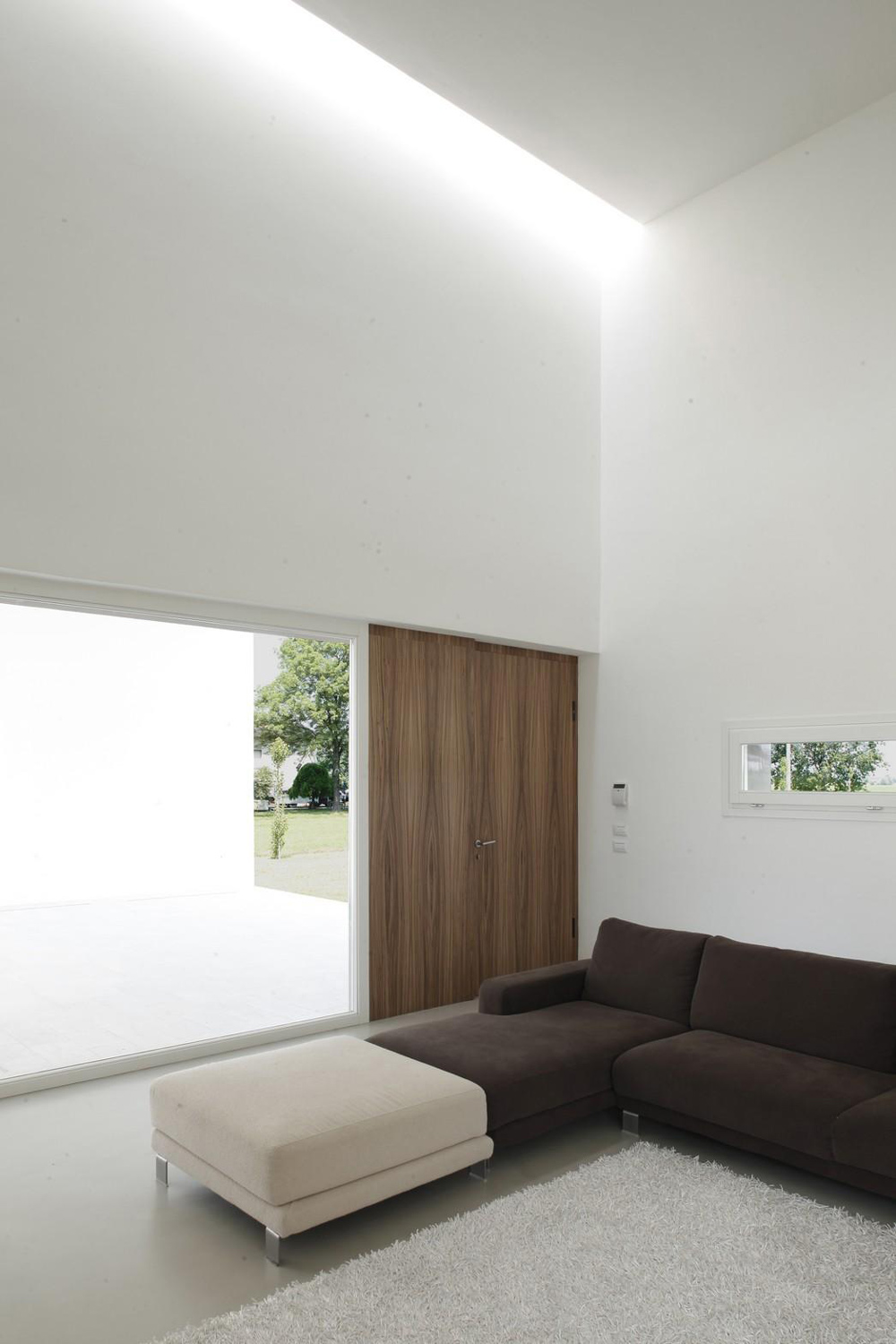 Front Door, Brown Sofa, Rug, Modern Eco-Friendly Home in Castelnovo di Sotto, Italy