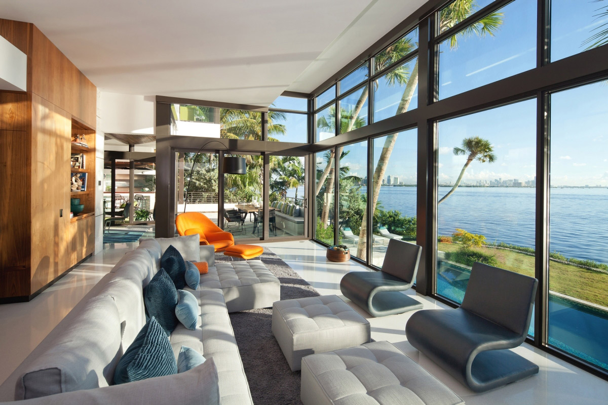 sofas living room glass walls waterfront residence in coral gables miami