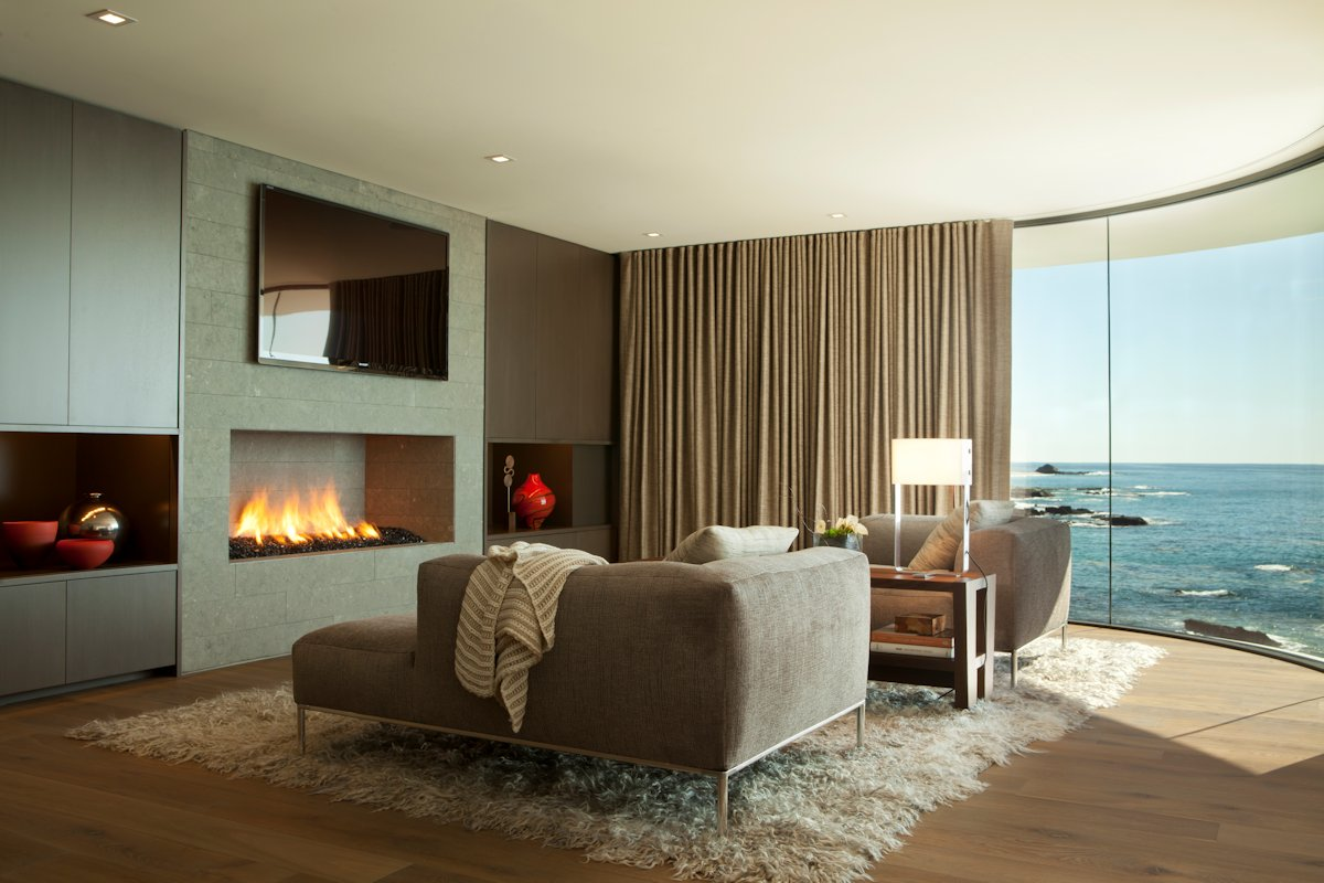 Modern fireplace rug sofa curved window beach house in laguna beach california