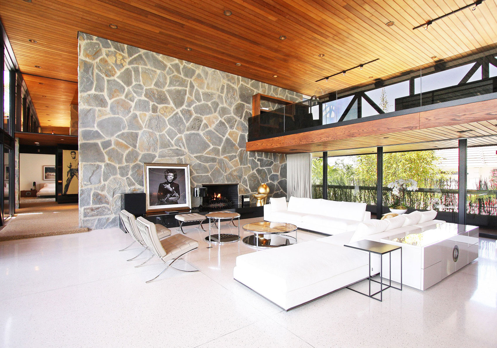 High Ceiling Living Room White Sofas Fireplace Stone Wall Revamped Interior In Beverly Hills